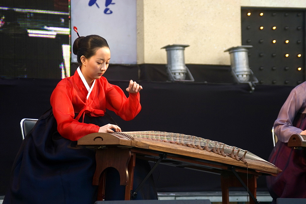Korean woman plays a Gayageum, a traditional zither like musical instrument at the Peace festival, Geoje-Do, South Korea, Asia