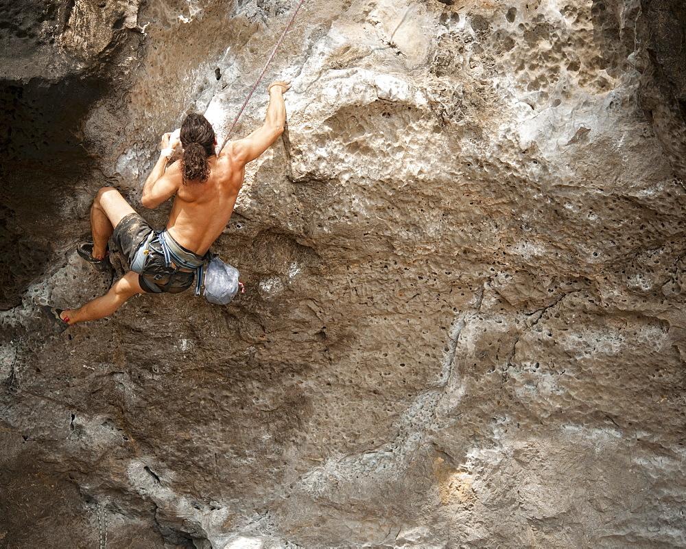 Adult male, rock climbing, Railay Beach.  Krabi, Thailand, South-East Asia, Asia