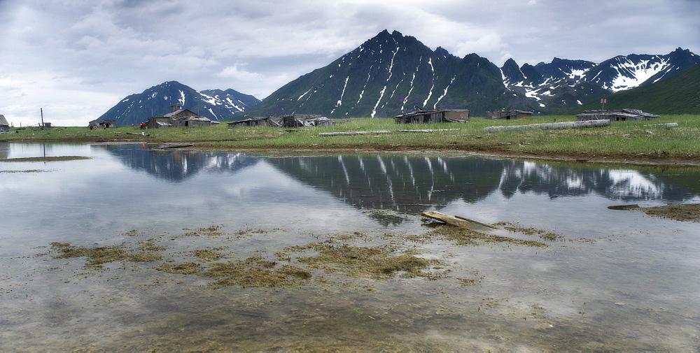 Abandoned Herring fishing settlement, tsunami damage, building debris, Landscape view of snow caped mountains, Yuzhnaya Glybokaya Bay (Bering Sea) Russia, Asia