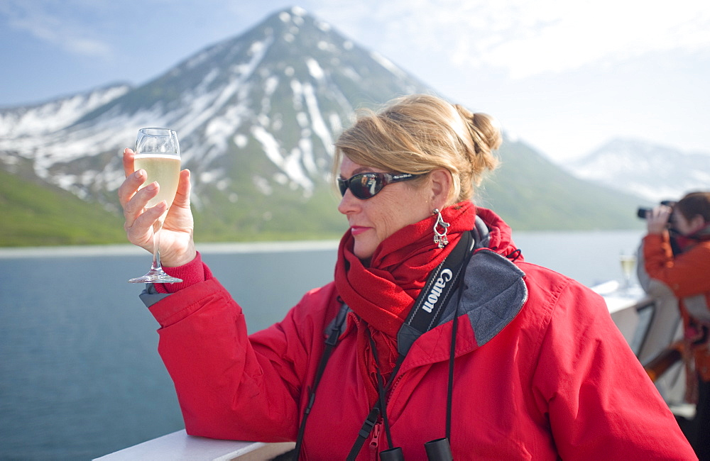 Views from the Clipper Odyssey towards Russkaya Bay of volcanic mountains in mist and sun set, Woman with champagne, Russkaya Bay (Bering Sea), Russia, Asia.