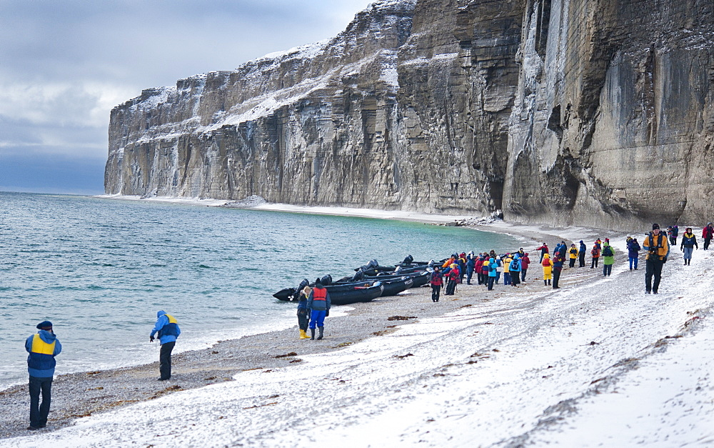 Tourist standing on snow covered arctic beach. Akpatok Island, Quebec, Nunavik, Canada, North America