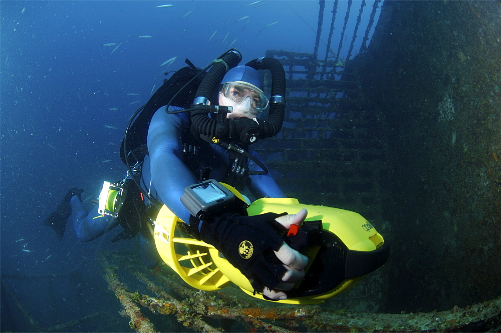 Mixed gas rebreather diver using scooter for mobility around  wreck.  Red Sea.