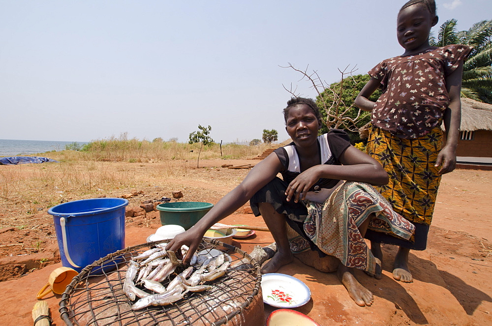 Lady preparing fish for meal with young girl, Talpia, Zambia, Africa