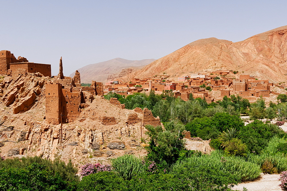 Green vegetation on the stream banks contrasts with the bare rock and mud bricks of ancient ruins and a mountain village, near the Dades Gorge, Morocco, North Africa, Africa