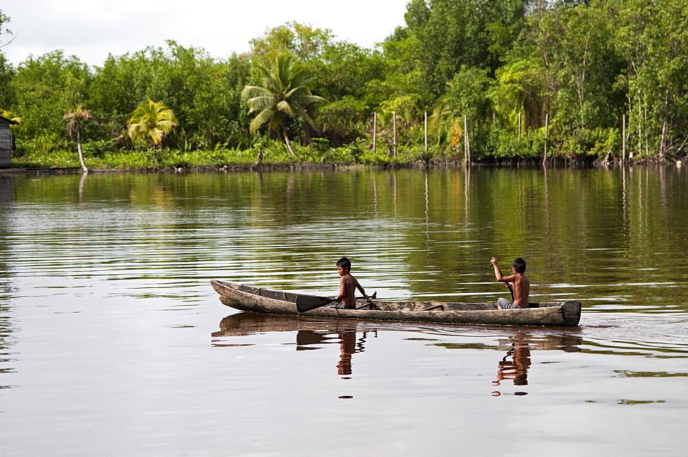 Amerindian boys paddling dugout canoe, Maharuma, Guyana, South America - 971-34