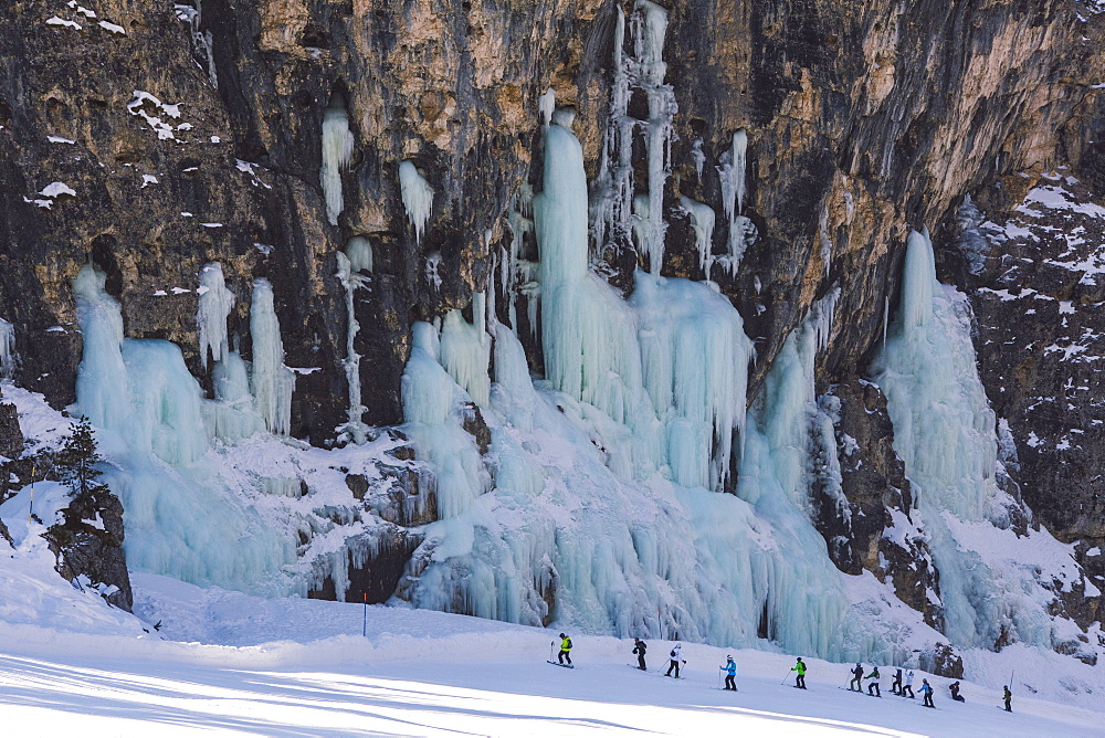 Skiers underneath the frozen waterfall, Hidden Valley ski area, Lagazuoi, Armentarola 101, Ski piste, Dolomites, UNESCO World Heritage Site, South Tyrol, Italy, Euruope