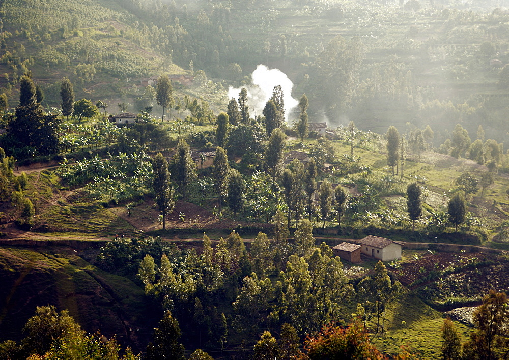 """A fire is smoking in the glow of the low sunlight.  The small manageable fields are like a patchwork quilt with the colours of the different crops laid out over """"the land of 1000 hills"""". Gikongoro, Rwanda, East Africa"""
