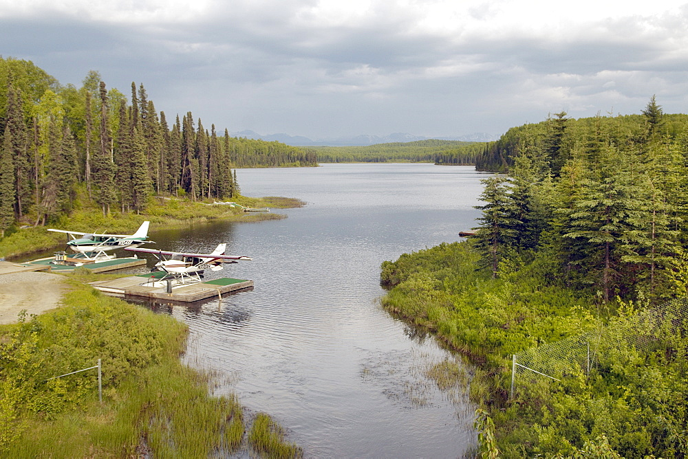 Two Boat Planes moored on an Alsakan Lake, surrounded by a  forrest.  The sky is heavy with cloud, good chance of rain.  Located in the Interior region of Alaska. The Interior, Alaska, USA