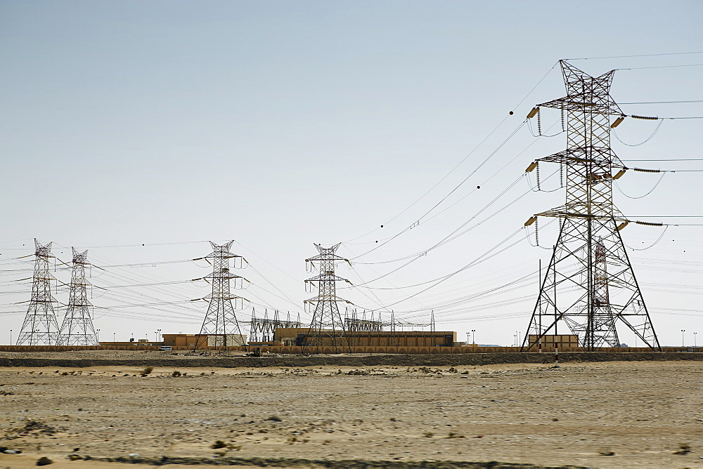 Electricity pylons dominate the flat barren landscape, pointing to civilisation somewhere, Qatar, Middle East - 975-243