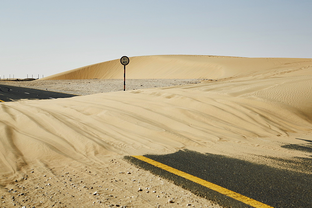 Sand dune blocks road in the Qatari desert, Qatar, Middle East