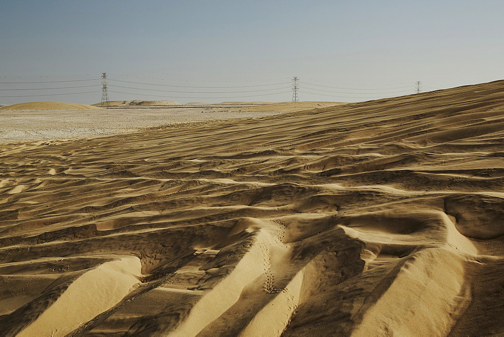 Sand dunes and electricity pylons dominate the desert landscape, Qatar, Middle East - 975-246