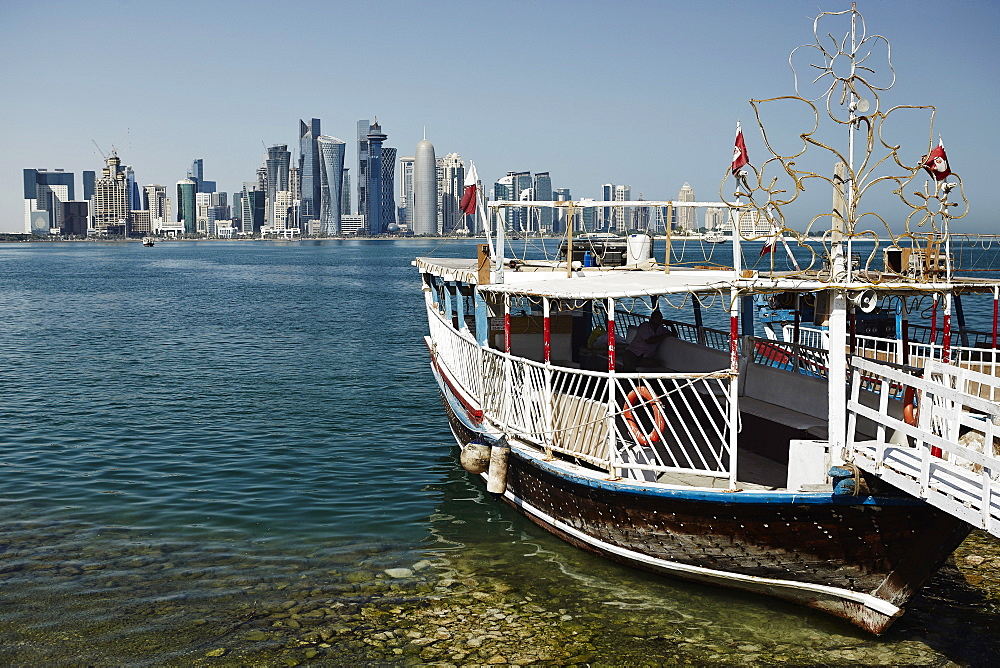 Downtown Doha with its impressive skyline of skyscrapers with authentic dhows in the bay, Doha, Qatar, Middle East - 975-251