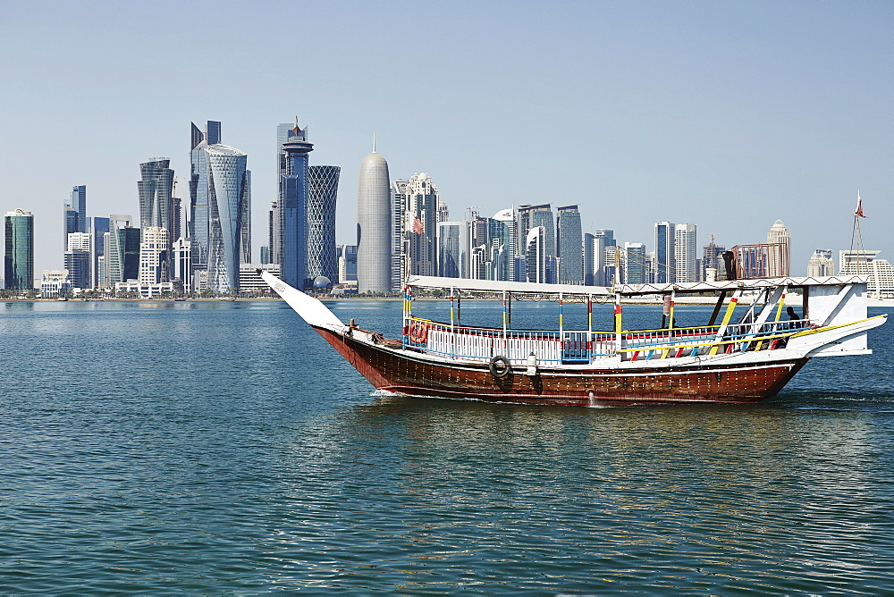 Downtown Doha with its impressive skyline of skyscrapers with authentic dhows in the bay, Doha, Qatar, Middle East
