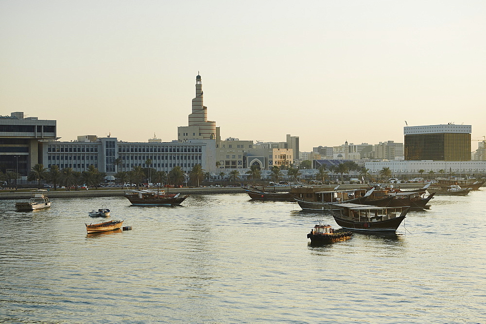 View from The Museum of Islamic Arts towards old Doha and The Islamic Centre with dhows moored in the Harbour at sunset, Doha, Qatar, Middle East