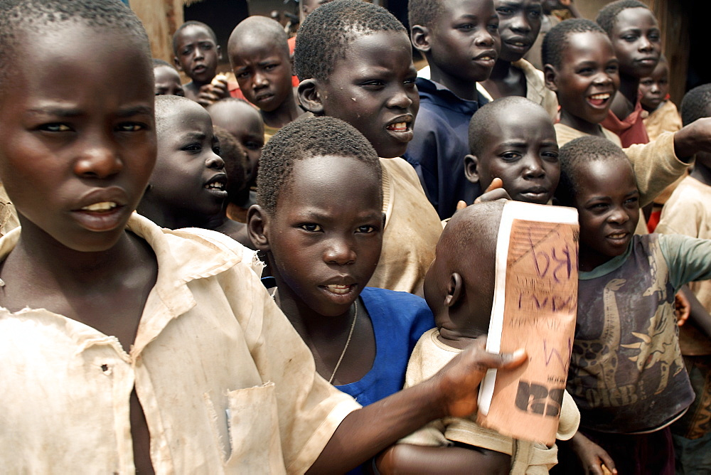 An IDP camp (internally displaced people) in Amuru district of Northern Uganda has been created to accommodate the mass of Ugandan refugees fleeing the LRA (Lords Resistance Army) who are fighting the Ugandan government and its people.  An inquisitive teenage boy is holding an exercise book. Amuru, Uganda, East Africa