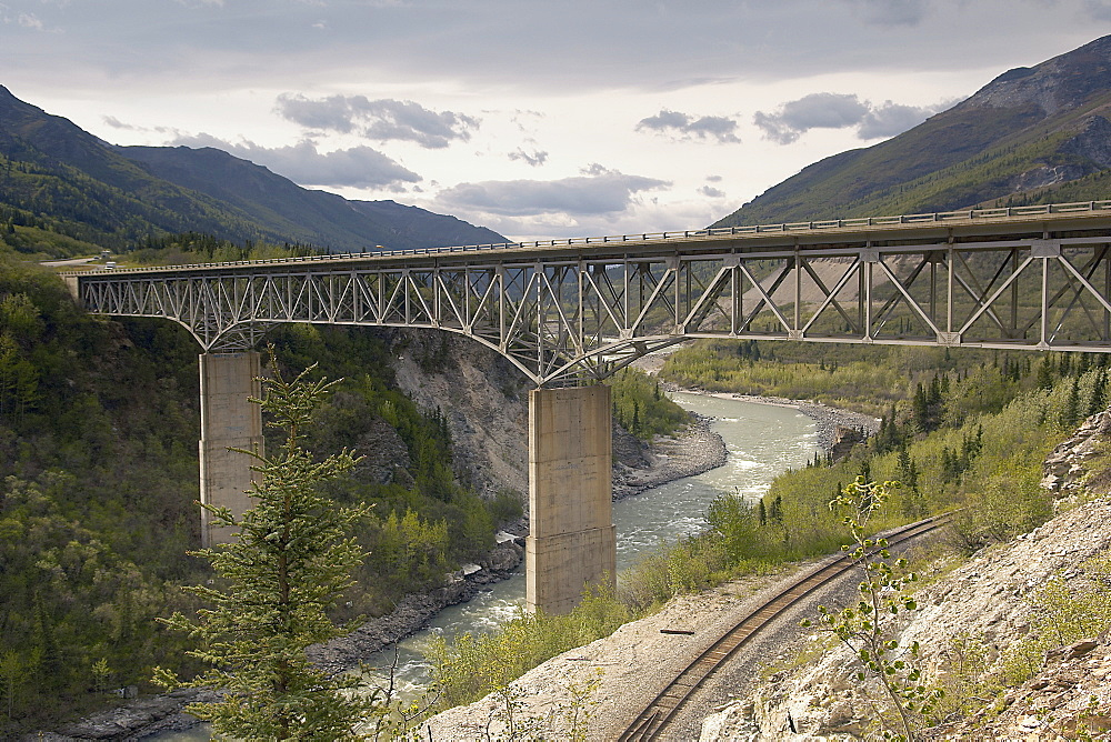 A truss road bridge crossing a Glacial river in the Alaskan Interior, Denali, spanning both the valley and a rail track.  Mountainous landscape in background. Denali, Alaska, USA