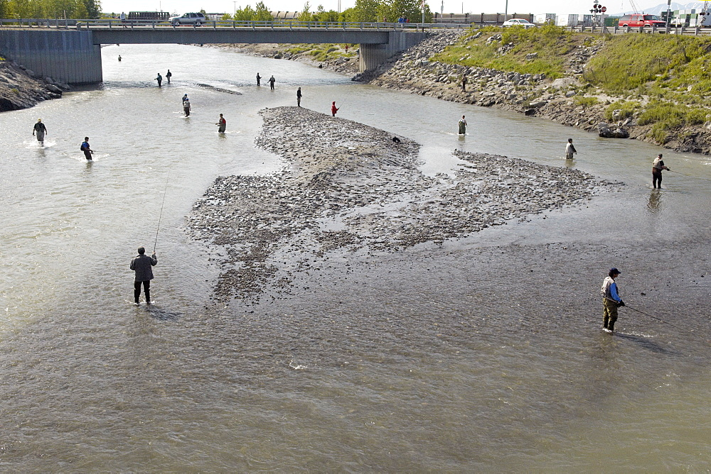 Fishing for Chinook Salmon, the fishermen of Anchorage come out in their droves to land a catch in the shallow setury of Ship Creek, downtown Anchorage, Alaska. Anchorage, Alsaka, USA