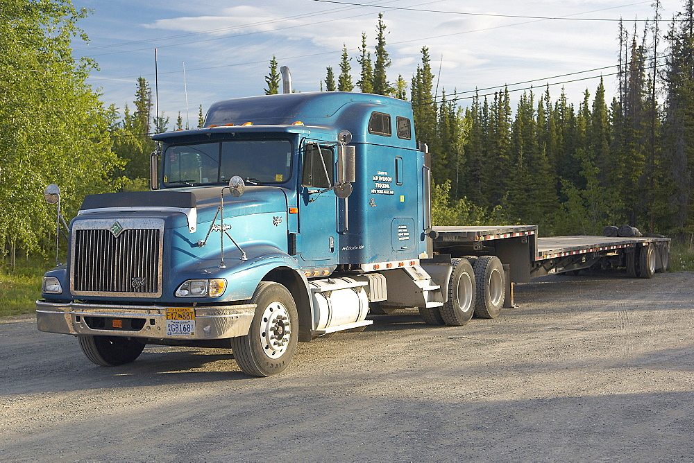 Blue Eagle, American Tractor with trailer attached.  Parked up in a layby next to a forest.  Sunny in the Alaskan Interior. The Interior, Alaska, USA