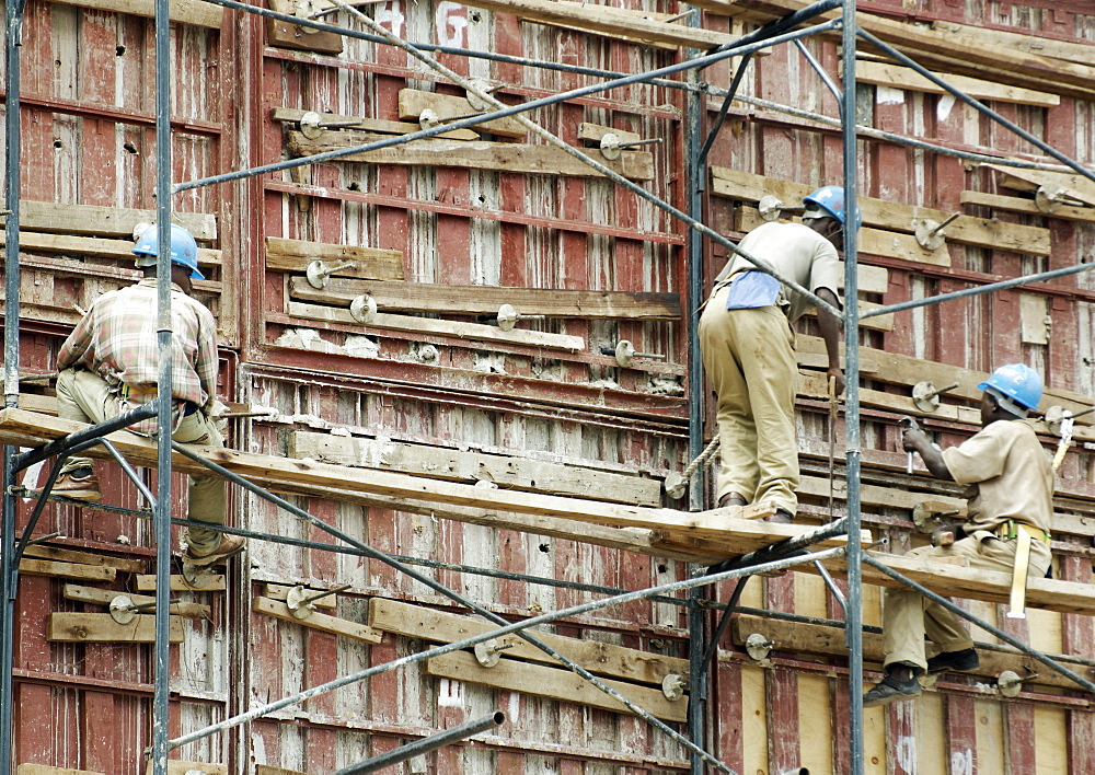 Three construction workers, all with safety hats work rather precariously on the meagre scaffolding, on a construction site in downtown Kigali, Rwanda. Kigali, Rwanda, East Africa