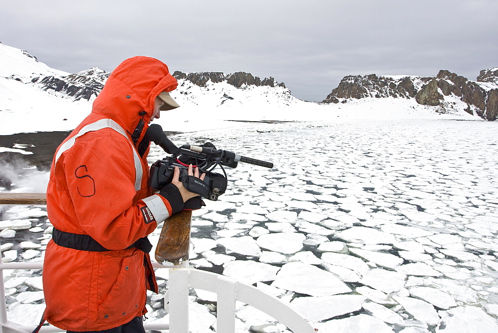 Crew videographer Anika of the Lindblad Expedition ship National Geographic Endeavour at work in the crows nest on Deception Island in Antarctica.