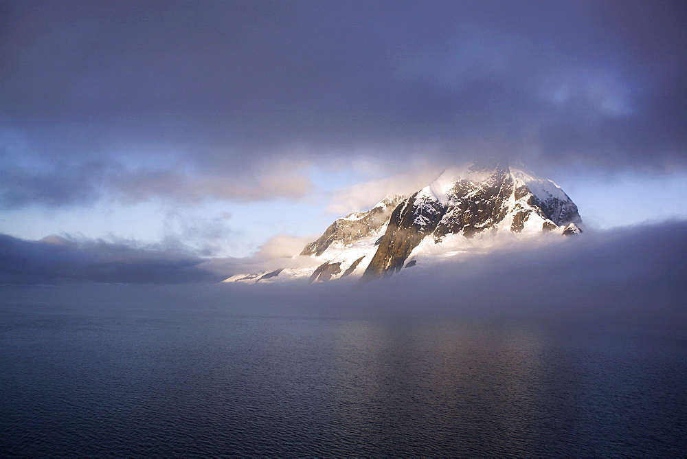 Shroud covered mountain peak in the magnificent Lemaire Channel, Antarctica.