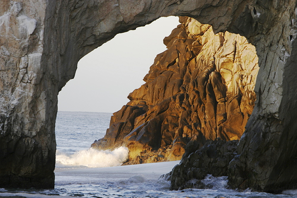 Sunrise on the famous finisterra arch at (land's end) rock formation in Cabo San Lucas, Baja California Sur, Mexico.