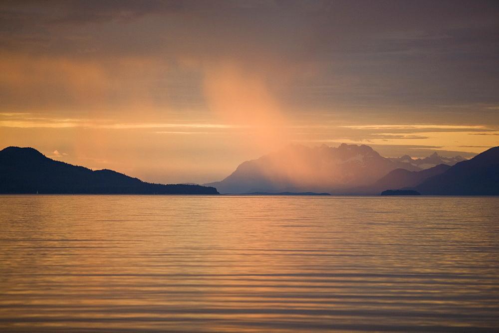 Sunset illuminating rain shower in Stephen's Passage near Juneau, Southeast Alaska, USA. Pacific Ocean.