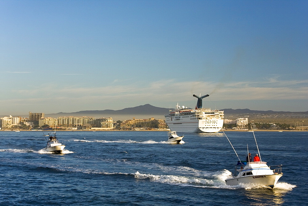 Sport fishing boats and cruise ship in the busy port of Cabo San Lucas, Baja California Sur, Mexico.