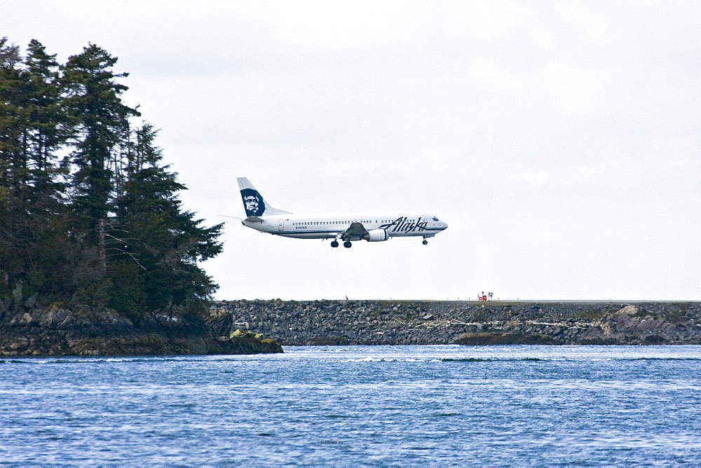 An Alaska Air commercial jet preparing to land at Sitka International Airport just outside the town of Sitka, southeast Alaska, USA.