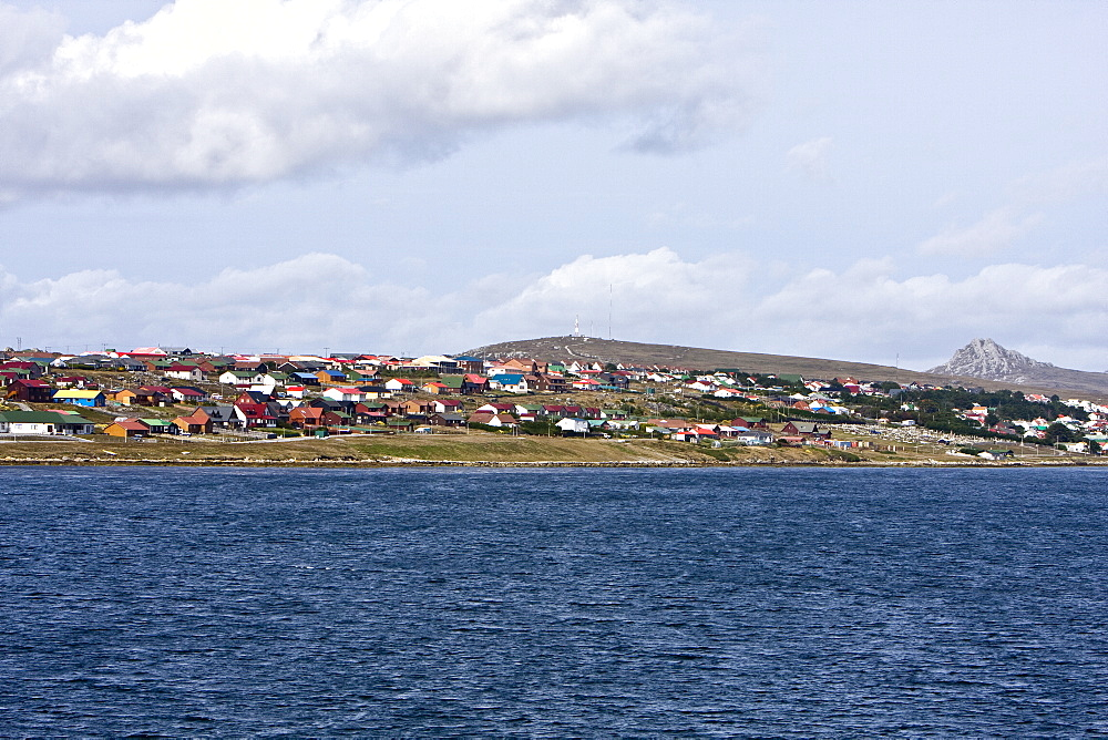 """Views from around Stanley (formerly known as """"Port Stanley""""), the capital and only true city (with a cathedral) in the Falkland Islands. It is located on the isle of East Falkland, on a north-facing slope, south of Stanley Harbour, in one of the wettest parts of the islands. As of the 2006 census, the city had a population of 2115. Stanley became the capital of the Falklands in July 1845. It was named for Lord Stanley, Secretary of State for War and the Colonies at the time. Stanley was occupied by Argentine troops for about ten weeks during the Falklands War in 1982 and renamed Puerto Argentino. Stanley suffered considerable damage during the war, a result of both the Argentine occupation and the British naval shelling of the town, which killed three civilians. After the British secured the high ground around the town the Argentines surrendered with no fighting in the town itself. The beaches and land around it were heavily mined and some areas remain marked minefields. Since the Falklands War, Stanley has benefited from the growth of the fishing and tourism industries in the Islands. Stanley itself has developed greatly in that time, with the building of a large amount of residential housing, particularly to the east of the town centre. Stanley is now over a third bigger than it was in 1982."""