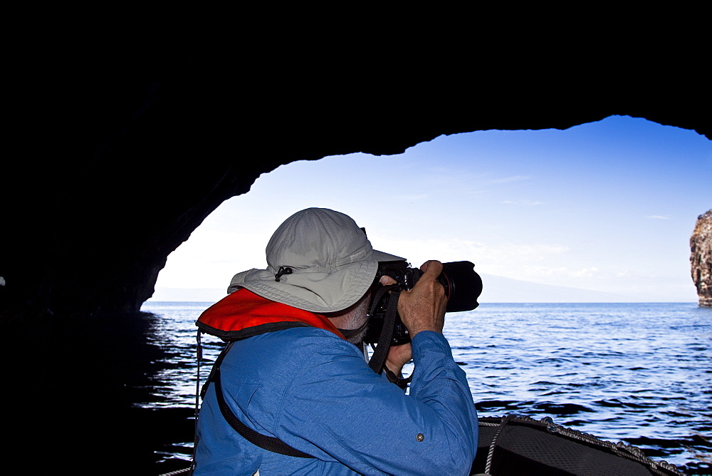 Lindblad Expeditions Guest taking photos inside sea grotto in the Galapagos Island Archipeligo, Ecuador. No model or property release are available for this image.
