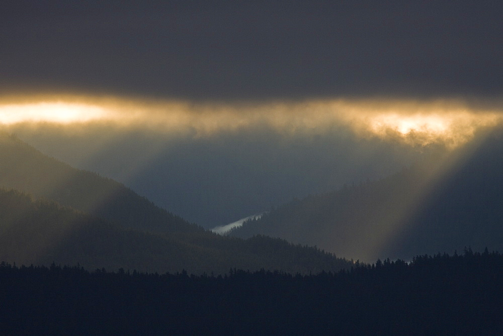 Dramatic early sunrise light over Admiralty Island from Chatham Strait in Southeast Alaska, USA. Pacific Ocean.