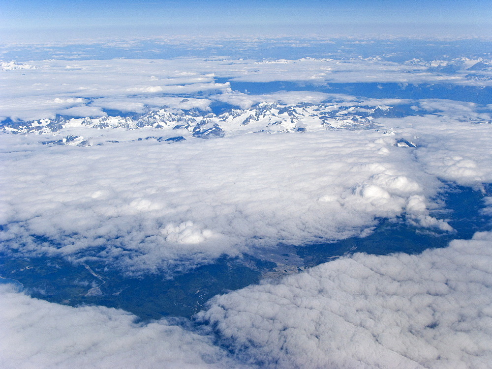 Aerial views of snow-capped mountains, ice fields, and glaciers on a commercial flight from Juneau to Anchorage Alaska, USA. Pacific Ocean. Alaska has hosted a glacier-favoring mixture of climate and topography for the last 12.5 million years. During the