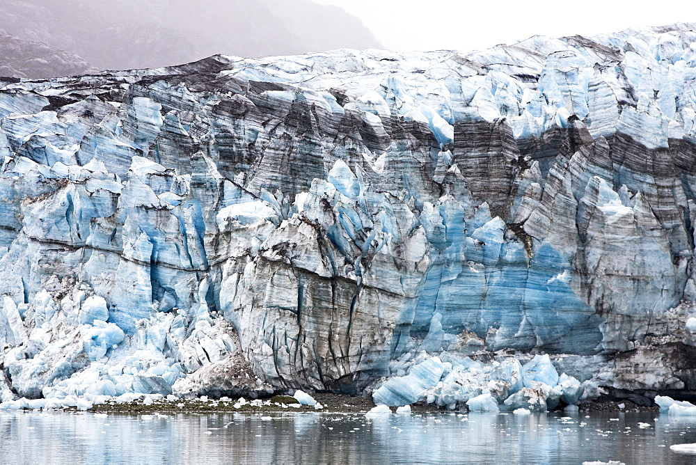 Lamplugh Glacier in Glacier Bay National Park, southeast Alaska, USA. Alaska is home to over 100,000 glaciers, many of them unamed. The Lamplugh Glacier is named for English Geologist George Lamplugh. Lamplugh Glacier is 150-180 feet above the waterline and 10-40 feet below. The Lamplugh is 3/4 mile wide, 16 miles long, and moving 1200 feet per year.