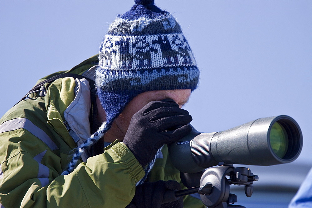 Guest from the Lindblad Expedition ship National Geographic Explorer looks through spotting scope in Antarctica