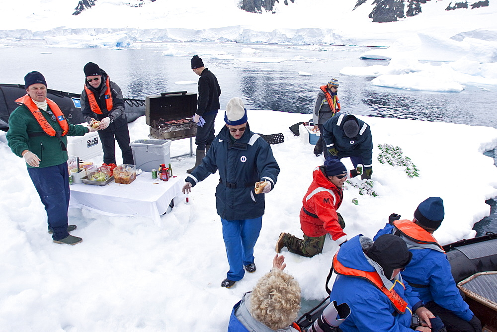 Guests from the Lindblad Expedition ship National Geographic Explorer enjoy a hot asado sandwich prepared by staff at BBQ on an ice floe near Adelaide Island, Antarctica. MORE INFO Lindblad Expeditions pioneered Antarctic travel in December 1969 and remains one of the premier Antarctic Expedition providers to this very day.