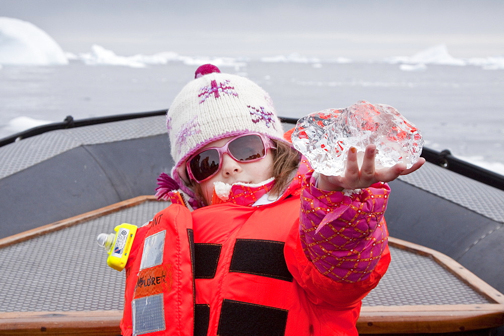 Guest Poppy (6) from the Lindblad Expedition ship National Geographic Explorer examines glacial ice near Petermann Island, Antarctica