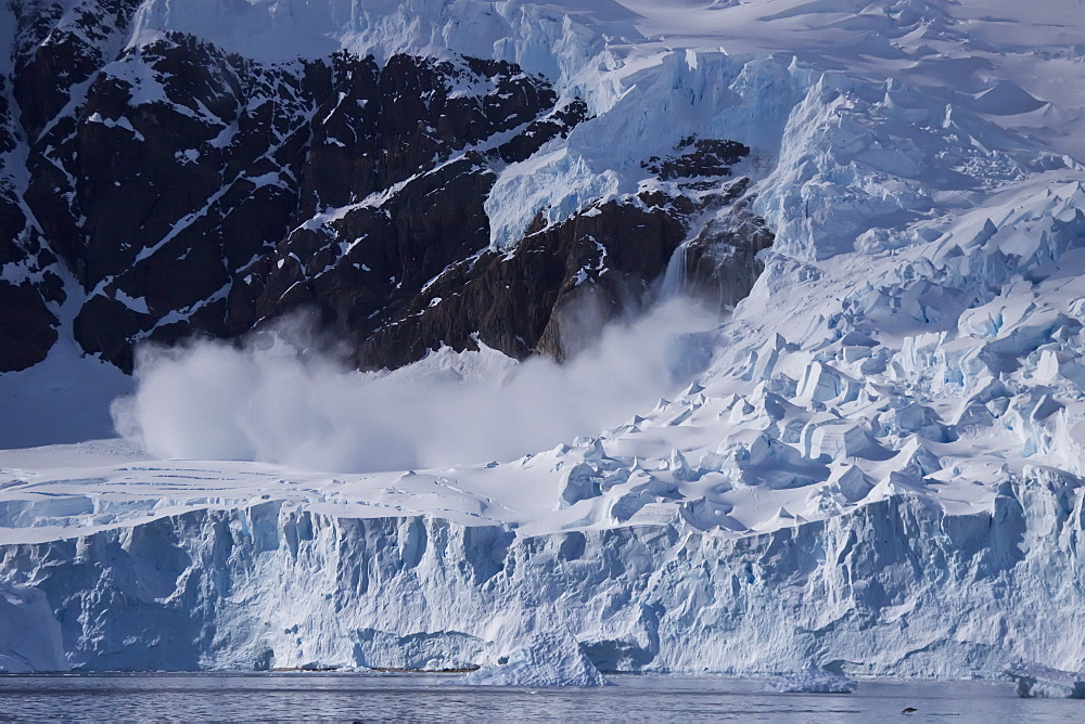 Small avalanche in Neko Harbour on the Antarctic Peninsula in Andvord Bay, Antarctica, Southern Ocean. MORE INFO Neko Harbour was named for a Norwegian whaling boat, the Neko, which operated in the area between 1911 and 1924.