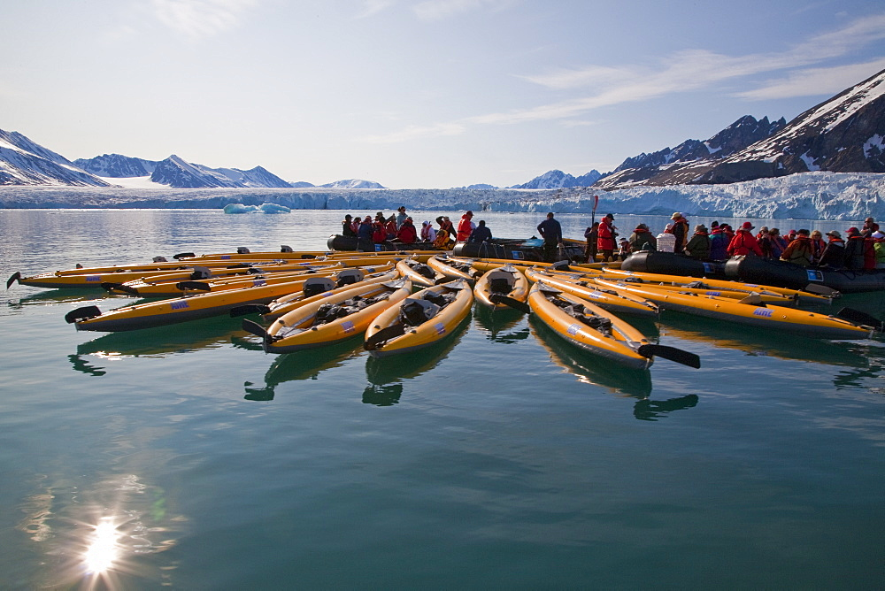Guests from the Lindblad Expedition ship National Geographic Explorer kayaking near Monaco Glacier on Spitsbergen Island in the Svalbard Archipelago in the summer months.