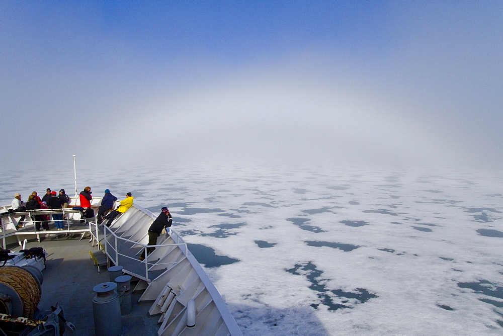Fog and a fog bow surround the Lindblad Expeditions ship National Geographic Explorer in Palanderbutka, Nordaustlandet, in the Svalbard Archipelago, Norway. MORE INFO Warm air meeting cooler, denser, moisture-laden air often lead to foggy conditions over ice floes in the summer here in Svalbard.