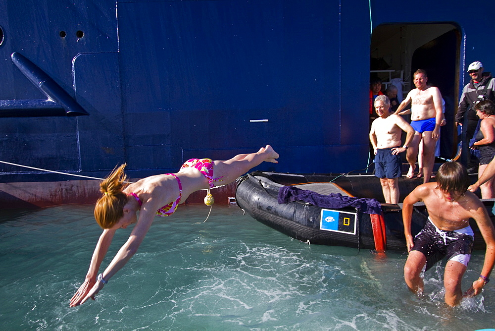 """Guests from the Lindblad Expedition ship National Geographic Explorer taking the """"polar plunge"""" in the Svalbard Archipelago, Norway"""