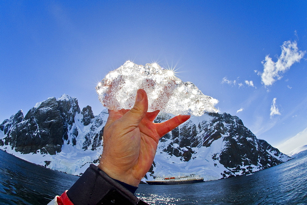 Ice held up to the sun near the Antarctic Peninsula during the summer months, Southern Ocean. MORE INFO An increasing number of icebergs are being created as climate change is causing the breakup of major ice shelves and glaciers all around the Antarctic Peninsula.