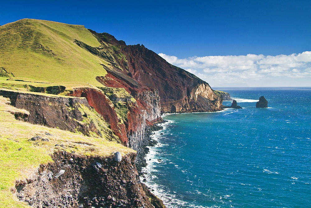 "View of the volcanic shoreline on Tristan da Cunha, ""the most remote inhabited location on Earth"", South Atlantic Ocean. MORE INFO The Tristan da Cunha Island Group is administered by the United Kingdom as part of the overseas territory of Saint Helena, A"