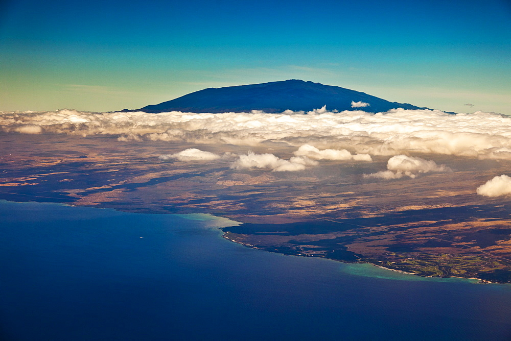 Mauna Kea, the tallest volcanic mountain in the chain of Hawaiian Islands, with its summit rising to the elevation of 13,796 ft (4,205 m) above sea level, observatories visible at summit, coastline of Kiholo Bay to Hualalai Resort below clouds, Big Island, Hawaii, USA - 983-574