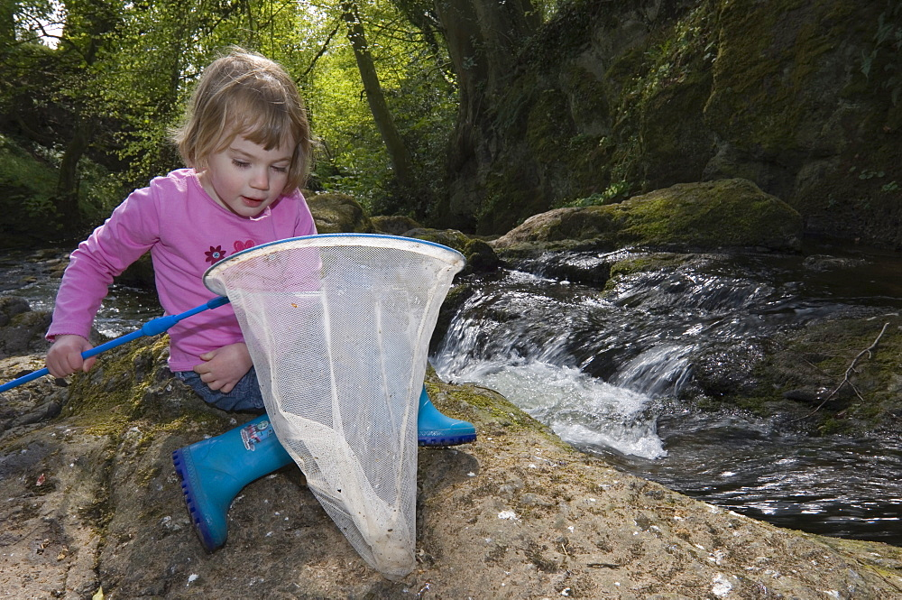 Young girl with net beside a waterfall, Arbirlot, Angus, Scotland - 987-393