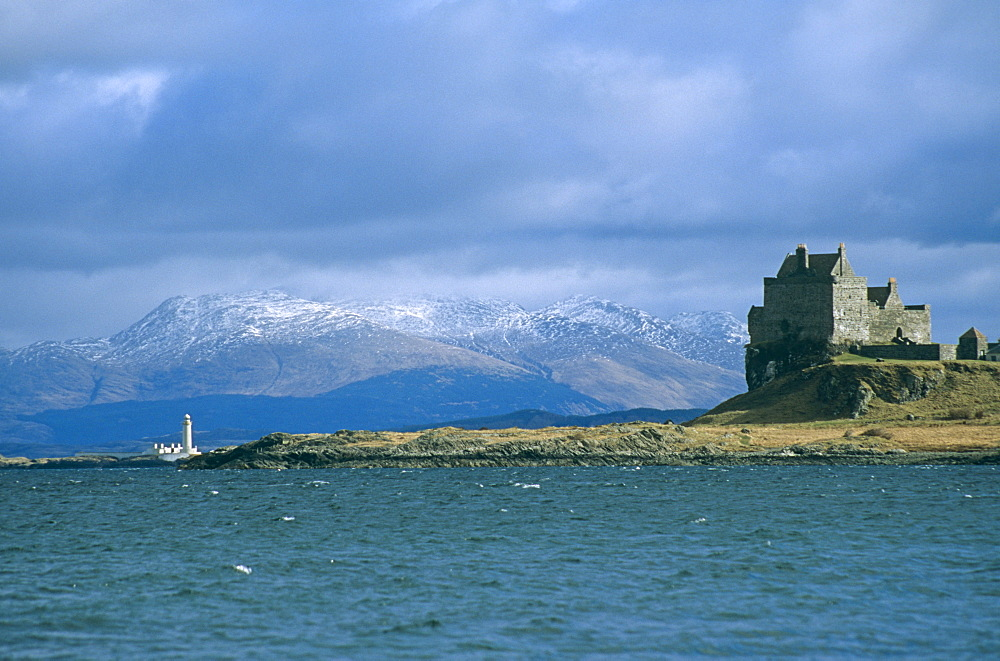 Duart Castle and the Lismore lighthouse.  the castle has been the home of the Clan Maclean since the 14th century. Isle of Mull, Scotland