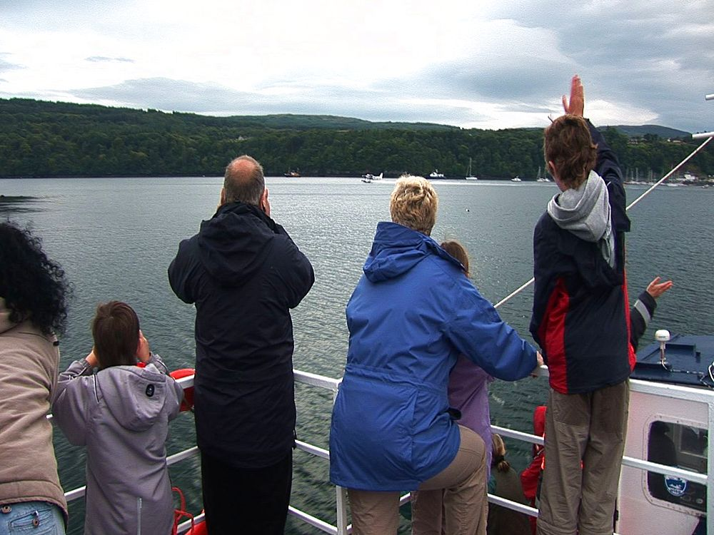 Whale watchers on boat, watch seaplane take off. Tobermory Harbour.Mull. UK. 22/07/08 - 988-480