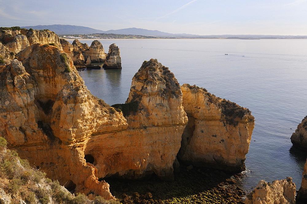 Weathered sandstone cliffs and sea stacks at Ponta da Piedade, Lagos, Algarve, Portugal, Europe