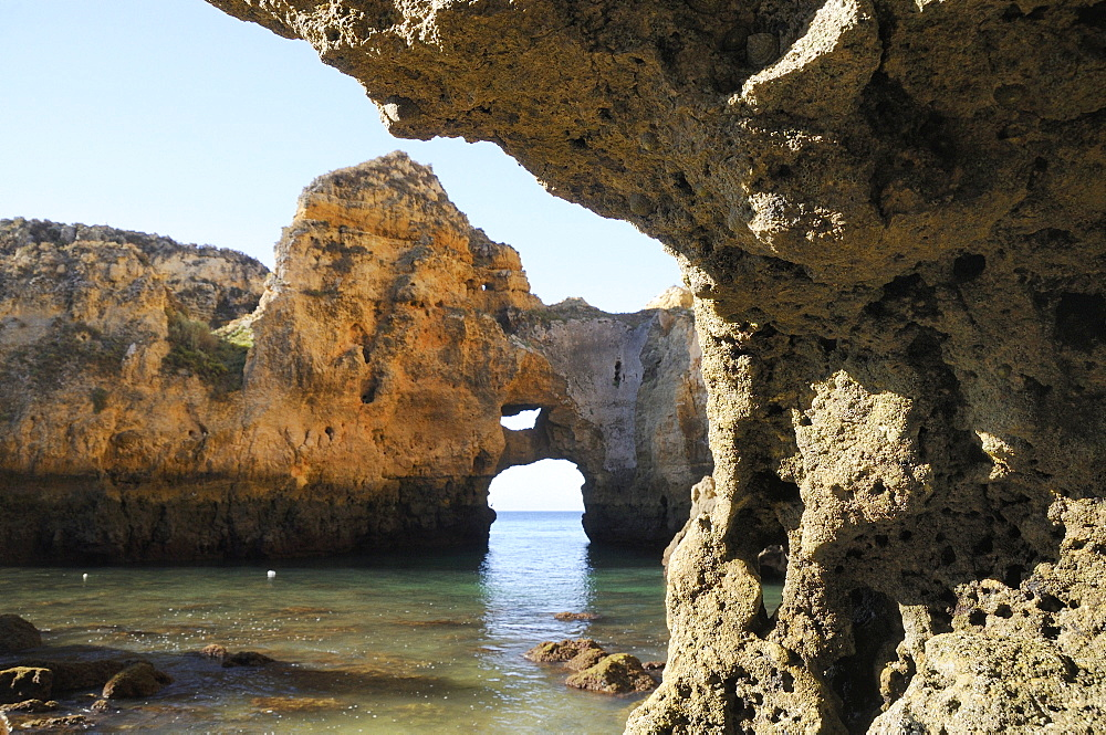 Weathered sandstone rocks and natural archway at Ponta da Piedade at low tide, Lagos, Algarve, Portugal, Europe