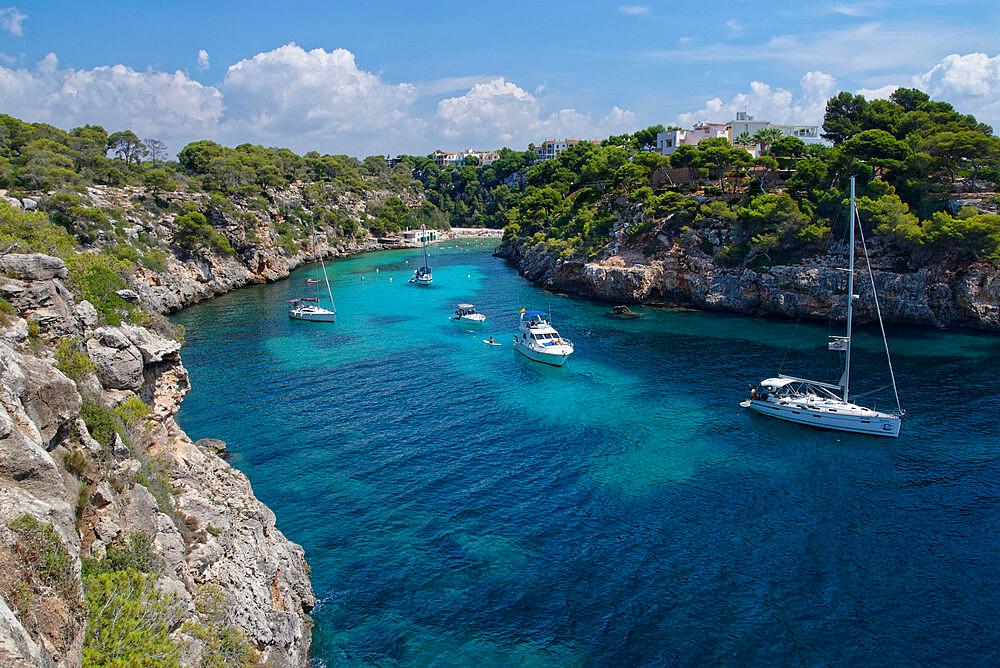 Yachts moored in the cove at Cala Pi, viewed from narrow cliff top coast path, Mallorca south coast. - 989-419